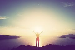 Szczęśliwa kobieta z rękami up na falezie nad morzem i wyspami przy zmierzchem Obraz Royalty Free