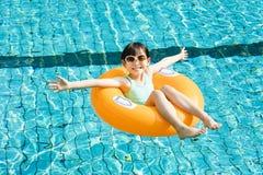 Szczęśliwa mała dziewczynka ma zabawę w pływackim basenie Obrazy Stock