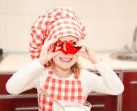 Szczęśliwa mała dziewczynka ma zabawę z formą dla ciastek w szefa kuchni kapeluszu Zdjęcia Royalty Free