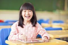 Szczęśliwa mała dziewczynka używa pastylkę lub ipad Zdjęcia Royalty Free