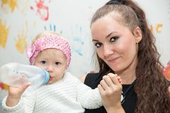 Szczęśliwa mama i dziewczynka pije od butelki Pojęcie dzieciństwo i rodzina Zdjęcia Stock