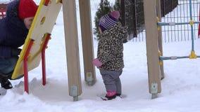 Szczęśliwa matka i dziewczynka zabawę pod śnieżną miecielicą w zimie 4K zdjęcie wideo