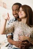 Szczęśliwa międzyrasowa para obejmuje szczęśliwie i pozuje wokoło kobiety od behind, mężczyzna mienie, biały pracowniany tło Zdjęcie Stock