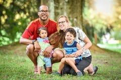 Szczęśliwa międzyrasowa rodzina cieszy się dzień w parku Fotografia Royalty Free