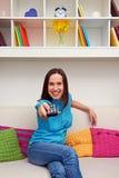 Szczęśliwa młoda kobieta ogląda tv Zdjęcie Royalty Free