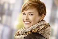 Szczęśliwa młoda kobieta przyglądająca z powrotem Fotografia Stock