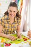 Szczęśliwa młoda kobieta robi dekoracyjnym jajkom Zdjęcia Stock