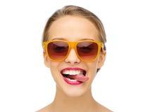 Szczęśliwa młoda kobieta w okularach przeciwsłonecznych pokazuje jęzor Zdjęcie Stock