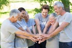 Szczęśliwa ochotnicza rodzina stawia ich ręki wpólnie Zdjęcie Royalty Free