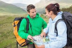 Szczęśliwa para odpoczywa po wycieczkować ciężką i ordynacyjną mapę Zdjęcia Stock