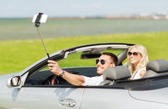 Szczęśliwa para w samochodzie bierze selfie z smartphone Zdjęcia Stock