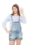Szczęśliwa potomstwo mody dziewczyna gestykuluje zadowalającego isolat w cajgów kombinezonach Zdjęcia Royalty Free