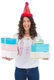 Szczęśliwa przypadkowa brunetka jest ubranym partyjne kapeluszowe mienie teraźniejszość Zdjęcie Royalty Free