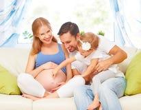szczęśliwa rodzina ciężarna matka, ojciec i dziecko córka przy hom, Obrazy Stock