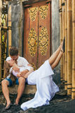 Szczęśliwa rodzina cieszy się romantycznego miesiąca miodowego wakacje na czarnej piasek plaży Obraz Stock