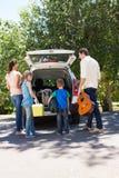 Szczęśliwa rodzina dostaje przygotowywający dla wycieczki samochodowej Obrazy Stock