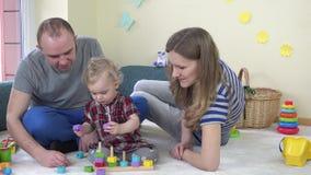 Szczęśliwa rodzinna ojciec córki i matki sztuka ciągnie kolorowe cegły na słupach zbiory wideo