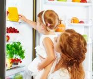 Szczęśliwa rodziny matka i dziecko córka pije sok pomarańczowego wewnątrz Fotografia Royalty Free