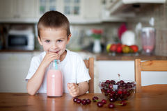 Szczęśliwa szkolna chłopiec pije zdrowego smoothie jako przekąska Obrazy Royalty Free