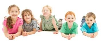 Szczęśliwa uśmiechnięta grupa dzieciaki na podłoga Zdjęcia Royalty Free