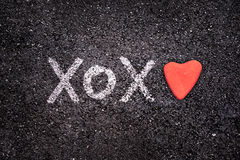 Szczęśliwa walentynka dnia karta, xoxo na ziemi i serce kamień, Obraz Royalty Free