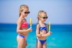 Szczęśliwe małe dziewczynki je lody podczas plaża wakacje Ludzie, dzieci, przyjaciele i przyjaźni pojęcie, Fotografia Stock