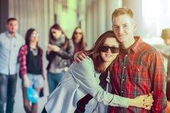 Szczęśliwe nastoletnie dziewczyny i chłopiec ma dobrą zabawę synchronizują outdoors Obraz Stock