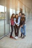 Szczęśliwe nastoletnie dziewczyny i chłopiec ma dobrą zabawę synchronizują outdoors Zdjęcia Stock