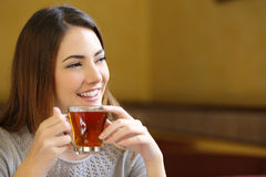 Szczęśliwej kobiety myślący mienie filiżanka herbata w sklep z kawą Zdjęcia Royalty Free