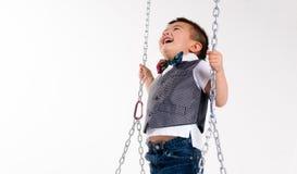 Szczęśliwej Młodej chłopiec sztuk huśtawki Zawieszony Poruszający Roześmiany dzieci bawią się Zdjęcia Stock