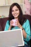 Szczęśliwej młodej kobiety driinking kawa Fotografia Stock