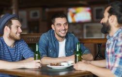 Szczęśliwi męscy przyjaciele pije piwo przy barem lub pubem Obrazy Royalty Free