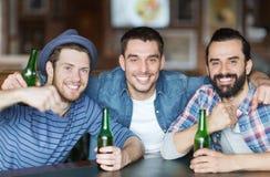Szczęśliwi męscy przyjaciele pije piwo przy barem lub pubem Zdjęcia Stock