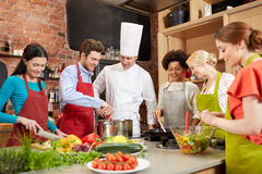 Szczęśliwi przyjaciele i szefa kuchni kucbarski kucharstwo w kuchni Fotografia Stock
