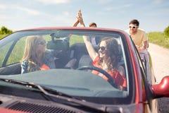 Szczęśliwi przyjaciele pcha łamającego kabrioletu samochód Zdjęcie Royalty Free