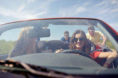 Szczęśliwi przyjaciele pcha łamającego kabrioletu samochód Zdjęcia Royalty Free
