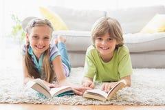 Szczęśliwi rodzeństwa trzyma książki podczas gdy kłamający na dywaniku Zdjęcia Royalty Free