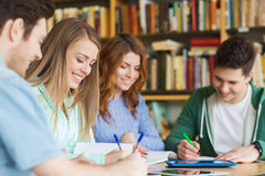 Szczęśliwi ucznie pisze notatniki w bibliotece Zdjęcia Royalty Free