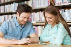 Szczęśliwi ucznie z pastylka komputerem osobistym w bibliotece Fotografia Stock