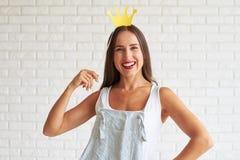 Szczęśliwy ładny brunetki mienie dekoruje koronę i ono uśmiecha się Obraz Stock