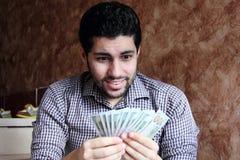 Szczęśliwy arabski młody biznesmen z dolarowymi rachunkami Zdjęcia Royalty Free