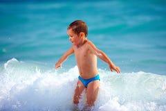 Szczęśliwy chłopiec dzieciak ma zabawę w wodzie morskiej Obrazy Royalty Free