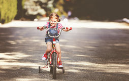 Szczęśliwy dziecko dziewczyny cyklista jedzie rower Obraz Stock
