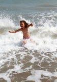Szczęśliwy dziecko przy morzem z fala Obraz Royalty Free