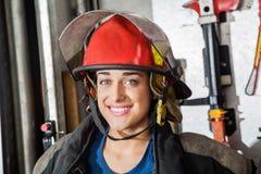 Szczęśliwy Żeński strażak Przy posterunkiem straży pożarnej Obrazy Stock