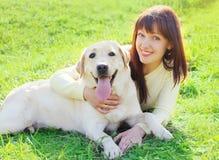 Szczęśliwy Labrador retriever właściciela i psa kobiety lying on the beach na trawie Zdjęcie Stock