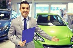 Szczęśliwy mężczyzna przy auto przedstawienia lub samochodu salonem Zdjęcia Royalty Free