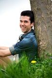 Szczęśliwy młodego człowieka obsiadanie w naturze Obrazy Royalty Free