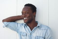 Szczęśliwy młody amerykanina afrykańskiego pochodzenia mężczyzna ono uśmiecha się przeciw białemu tłu Obraz Royalty Free