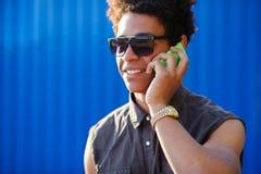 Szczęśliwy młody czarnego afrykanina mężczyzna z telefonem komórkowym ma rozmowę na wiszącej ozdobie Obraz Stock
